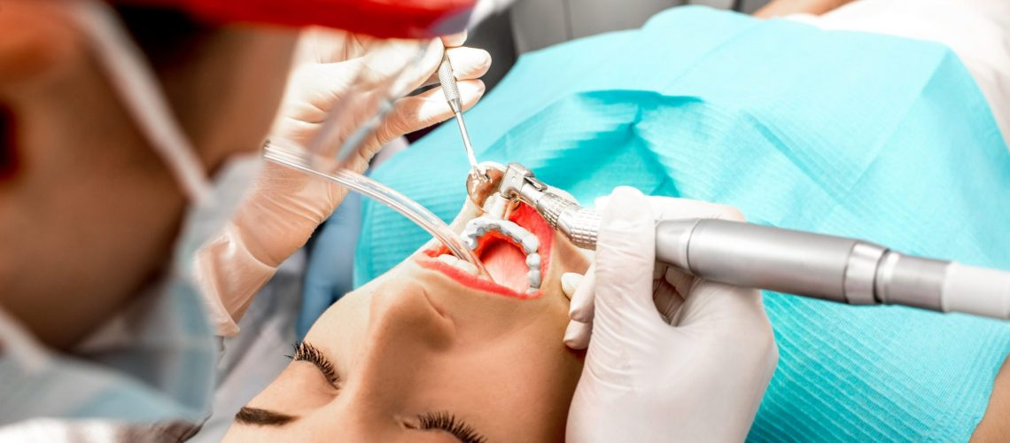 Dentist making professional teeth cleaning female young patient at the dental office