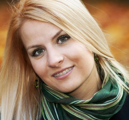 Portrait of smiling young blond woman over yellow autumn leaves, 25-30 years old