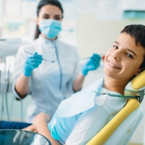Smiling little boy in a dental chair, professional pediatric dentistry, children stomatology, female dentist on background